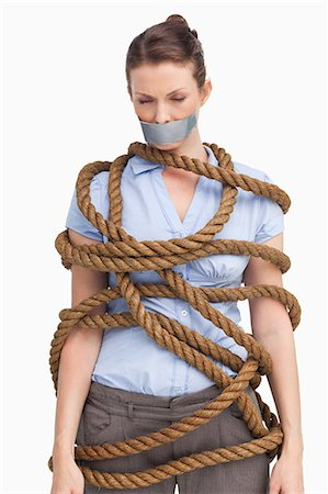 Businesswoman tied up against a white background Stock Photo - Premium Royalty-Free, Code: 6109-06005678