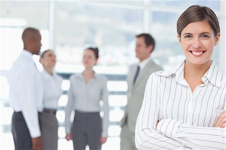 Smiling young saleswoman with arms crossed and colleagues behind her Stock Photo - Premium Royalty-Free, Code: 6109-06005699