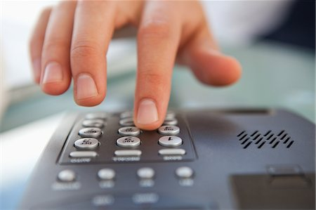 Close-up of a man dialing a telephone number on a landline phone Stock Photo - Premium Royalty-Free, Code: 6109-06005615