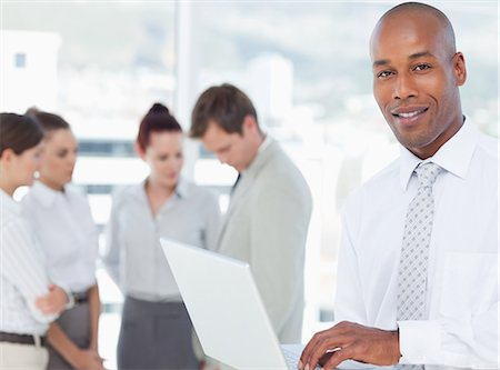 staff - Smiling young salesman with his laptop and associates behind him Stock Photo - Premium Royalty-Free, Code: 6109-06005741