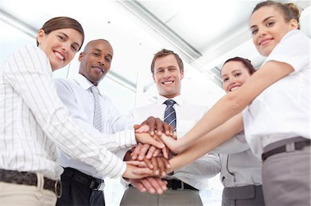 piles of work - Smiling young salesteam putting their hands together for a teamwork gesture Stock Photo - Premium Royalty-Free, Code: 6109-06005791