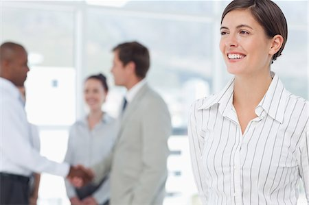 staff - Cheerful smiling young saleswoman with colleagues behind her Stock Photo - Premium Royalty-Free, Code: 6109-06005723