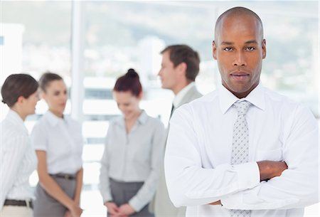 staff - Confident young salesman with arms crossed and colleagues behind him Stock Photo - Premium Royalty-Free, Code: 6109-06005725