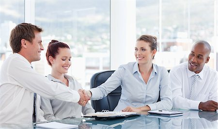Young businesspeople shaking hands while sitting at a table Stock Photo - Premium Royalty-Free, Code: 6109-06005845