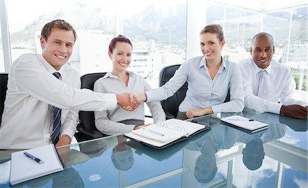 Smiling young businesspeople shaking hands while sitting at a table Stock Photo - Premium Royalty-Free, Code: 6109-06005848