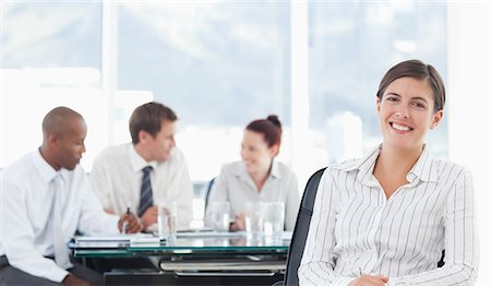 staff - Smiling young tradeswoman with meeting being held behind her Stock Photo - Premium Royalty-Free, Code: 6109-06005861