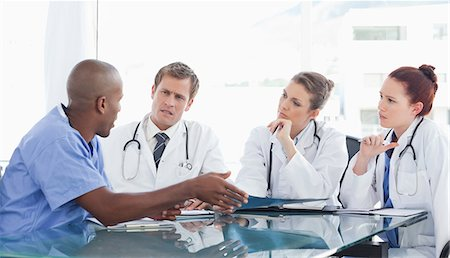A nurse talks with the three doctors in an office. Stock Photo - Premium Royalty-Free, Code: 6109-06005870