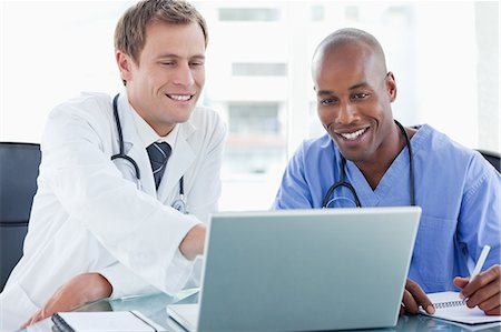 Smiling doctors working together with laptop Stock Photo - Premium Royalty-Free, Code: 6109-06005886