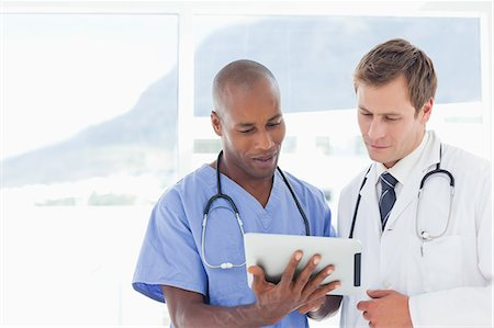 Standing doctors using tablet computer together Stock Photo - Premium Royalty-Free, Code: 6109-06005906
