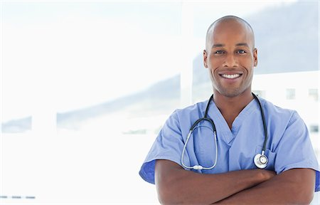 Smiling doctor with his arms crossed Stock Photo - Premium Royalty-Free, Code: 6109-06005915