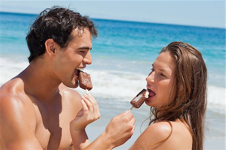 Close-up of lovers eating Popsicle together with sea in background Stock Photo - Premium Royalty-Free, Code: 6109-06006077