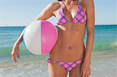 Close-up of an attractive woman body holding a beach ball with the sea in background Stock Photo - Premium Royalty-Free, Code: 6109-06006193
