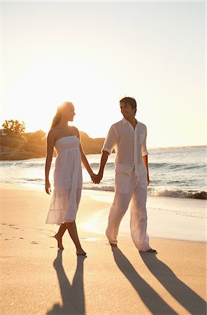romanticism - Young couple walking on the beach at sunset while holding their hands Stock Photo - Premium Royalty-Free, Code: 6109-06006294