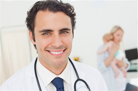 Smiling young doctors with his patients behind him Stock Photo - Premium Royalty-Free, Code: 6109-06006491