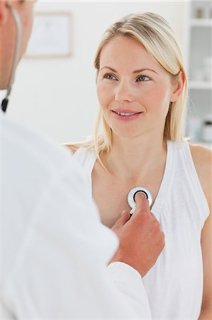 Woman getting her heart beat checked by her male doctor Stock Photo - Premium Royalty-Free, Code: 6109-06006432