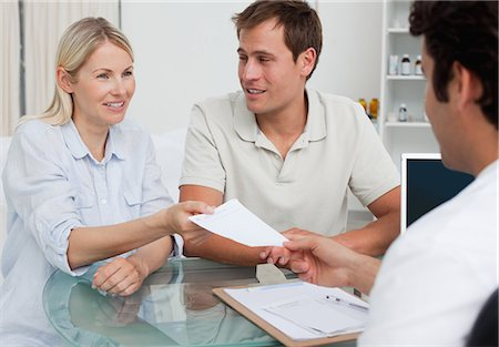 Young couple receiving prescription from their doctor Stock Photo - Premium Royalty-Free, Code: 6109-06006697