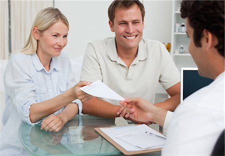 Doctor giving prescription to happy young couple Stock Photo - Premium Royalty-Free, Code: 6109-06006698