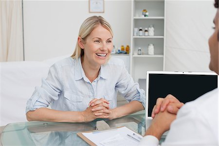 Happy smiling woman seeing her doctor Stock Photo - Premium Royalty-Free, Code: 6109-06006703