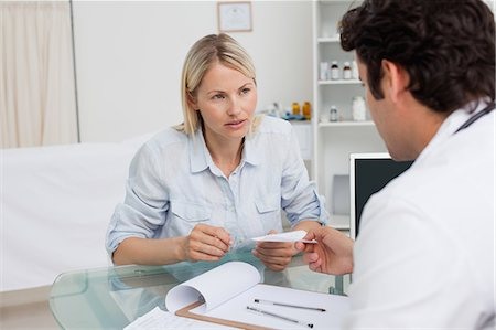 Worried looking woman getting prescription from her doctor Stock Photo - Premium Royalty-Free, Code: 6109-06006707