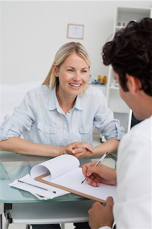 Smiling woman getting good test results from her doctor Stock Photo - Premium Royalty-Free, Code: 6109-06006705