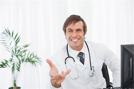 Smiling doctor extending his hand while sitting behind his desk with a computer on it Stock Photo - Premium Royalty-Free, Code: 6109-06006851