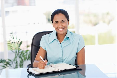secretary desk - Smiling secretary looking at the camera while writing on a diary Stock Photo - Premium Royalty-Free, Code: 6109-06006973