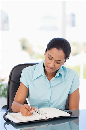 secretary desk - Relaxed secretary ar work is writing on her dairy while sitting at a desk Stock Photo - Premium Royalty-Free, Code: 6109-06006971