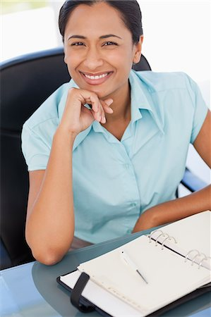 secretary desk - Smiling secretary placing her hand on her chin while sitting in front of a diary Stock Photo - Premium Royalty-Free, Code: 6109-06006983