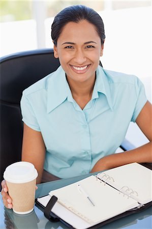 secretary desk - Secretary sitting at a desk while showing a beaming smile in front of the camera Stock Photo - Premium Royalty-Free, Code: 6109-06006980