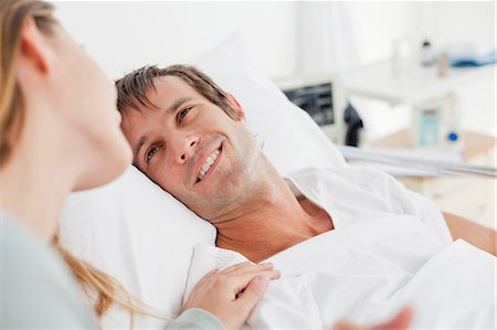 people hospital - Smiling patient looking at his girlfriend while lying in a hospital bed Stock Photo - Premium Royalty-Free, Code: 6109-06007082