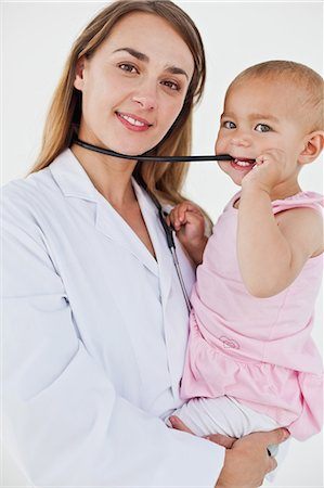 Lovely baby chewing the stethoscope of the nurse who is holding her Stock Photo - Premium Royalty-Free, Code: 6109-06007094