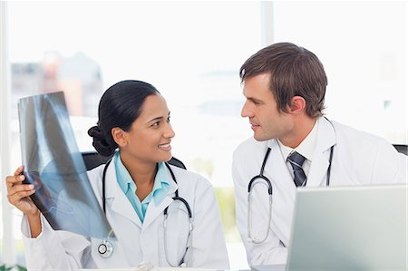 Relaxed doctor holding a chest x-ray while smiling and looking at her colleague Stock Photo - Premium Royalty-Free, Code: 6109-06007001