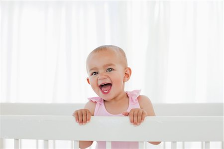 Little baby shouting loudly while standing up in her bed Stock Photo - Premium Royalty-Free, Code: 6109-06007023