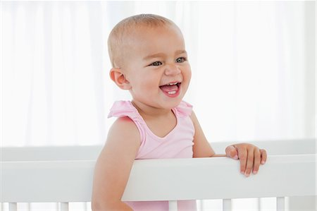 Little baby laughing while standing up in her white bed Stock Photo - Premium Royalty-Free, Code: 6109-06007027