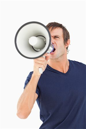 Furious man using a megaphone while shouting against a white background Stock Photo - Premium Royalty-Free, Code: 6109-06007147