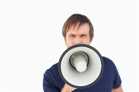 Furious man shouting while using a megaphone against a white background Stock Photo - Premium Royalty-Free, Code: 6109-06007144