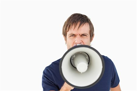 Furious man using a megaphone to talk against a white background Stock Photo - Premium Royalty-Free, Code: 6109-06007145