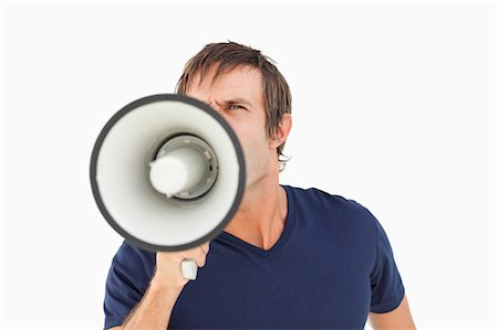 Furious man holding a megaphone while standing up against a white background Stock Photo - Premium Royalty-Free, Code: 6109-06007146