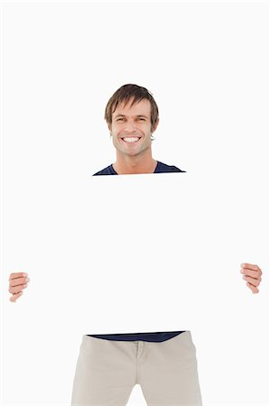 poster - Smiling man holding a blank poster against a white background Stock Photo - Premium Royalty-Free, Code: 6109-06007151