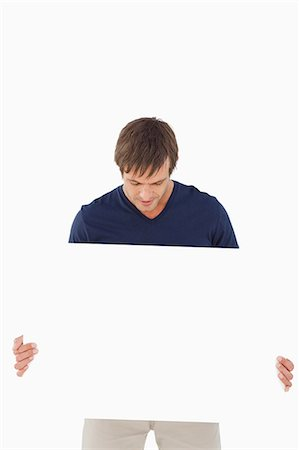 poster - Calm man holding a blank poster while leaning his head against a white background Stock Photo - Premium Royalty-Free, Code: 6109-06007152