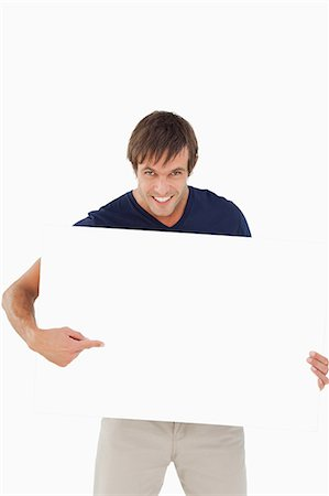 poster - Smiling man pointing a blank poster against a white background Stock Photo - Premium Royalty-Free, Code: 6109-06007154