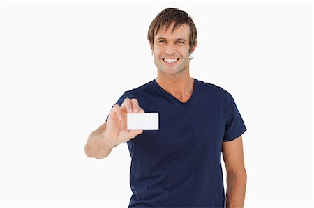 Smiling man holding a blank business card against a white background Stock Photo - Premium Royalty-Free, Code: 6109-06007167