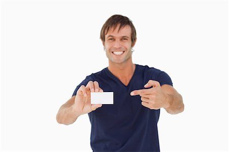 Blank business card being shown by a young man against a white Stock Photo - Premium Royalty-Free, Code: 6109-06007169