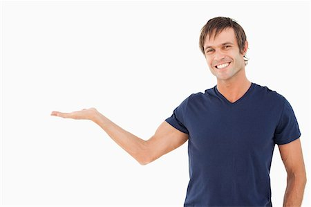 displaying - Smiling man staring at the camera while standing up and holding his palm up Stock Photo - Premium Royalty-Free, Code: 6109-06007109