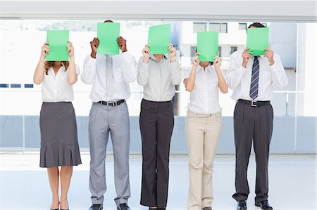 person holding sign - Business team holding green sheets in front of their face as they stand together Stock Photo - Premium Royalty-Free, Code: 6109-06007349