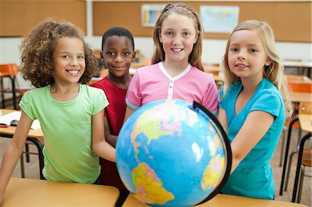 elementary school - Elementary students standing behind globe Stock Photo - Premium Royalty-Free, Code: 6109-06007392