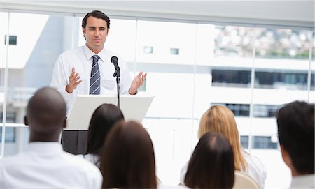 Black haired businessman gestures towards an audience who are watching him Stock Photo - Premium Royalty-Free, Code: 6109-06007300