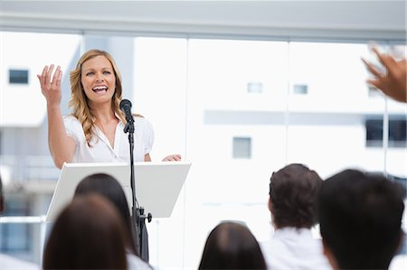 Businesswoman laughing as she gestures to a member of an audience who has his arms raised Stock Photo - Premium Royalty-Free, Code: 6109-06007302