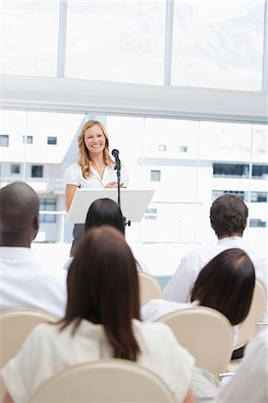 Woman smiling as she looks ahead at an audience who are watching her Stock Photo - Premium Royalty-Free, Code: 6109-06007304