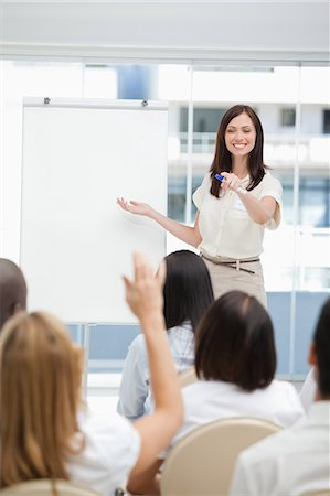showing - Woman smiling as she points to the audience during a presentation Stock Photo - Premium Royalty-Free, Code: 6109-06007334